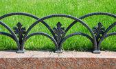 Decorative fencing near sidewalk in park — Stock Photo