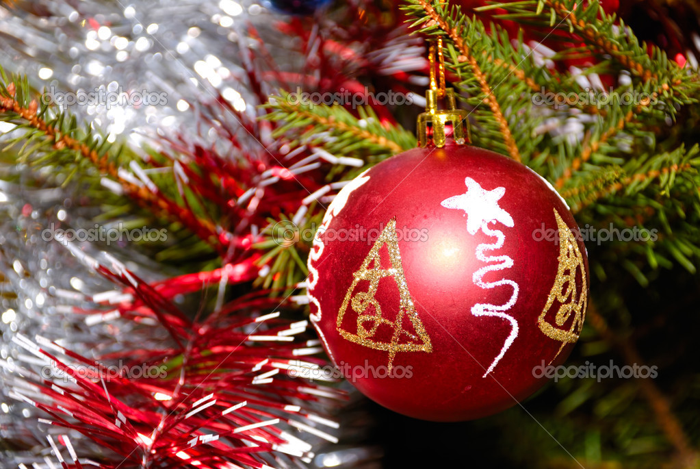 Red xmas ball hanging on fir tree with other decoration — Stock Photo #12117134