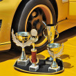 Trophies and yellow racing car — Stock Photo