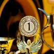 Trophies for winner and yellow wheel of racing car — Stock Photo