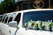 White wedding limousine with flowers — Stock Photo