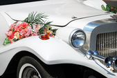 White wedding limousine with flowers — Stock Photo