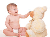 Smiling baby playing with teddy bear — Stock Photo