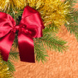 Fir branches with red bow on golden background - Stock Photo