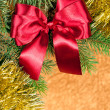 Fir branches with red bow on golden background — Stock Photo #14911705