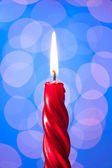 Red candle light on blue background — Stockfoto
