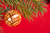 Christmas golden ball on red — Stock Photo