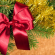 Fir branches with red bow on golden background — Stock Photo #15882227