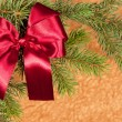 Stock Photo: Fir branches with red bow on golden background