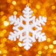 One big snowflake toy on golden bokeh background — Стоковая фотография