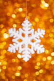 One big snowflake toy on golden bokeh background — Stockfoto