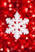 One big snowflake toy on red bokeh background — Stock Photo