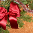 Fir branches with red bow on golden background — Stock Photo
