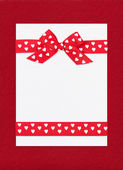 Red bow on paper sheet — Stock Photo