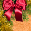 Fir branches with red bow on golden background — Stock Photo #18651717