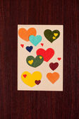 Card with hearts on wooden background — Stockfoto