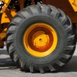 Big wheel on yellow tractor - Stok fotoğraf