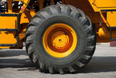 Big wheel on yellow tractor — Stock Photo