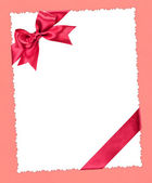 Blankopapier blatt mit roter schleife auf rosa — Stockfoto