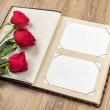 Photo album and roses on wooden — Stock Photo #23114978