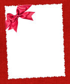 Blank paper sheet with red bow on red textile — Stock Photo