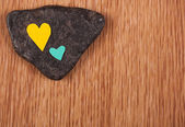 Hearts on stone and wooden background — Stock Photo