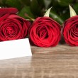 Three red roses and blank sheet on wood — Stock Photo