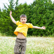 Boy jumping on flower meadow  — Stock Photo
