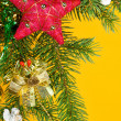 Christmas fir tree decoration on yellow — Stock Photo