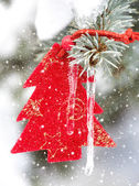 Christmas tree toy in snowfall with icicle — Stock Photo