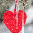Red heart toy on fir tree with snowfall — Stock Photo