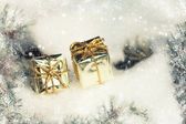Golden gift boxes on winter tree with snowfall — Stock Photo