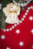 Christmas decoration and angel toy on red textile — Stock Photo