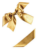 Golden bow made from silk ribbon — Stock Photo