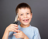 Boy holds a lost tooth in the pliers — Stock Photo
