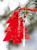 Christmas tree toy in snow with icicle — Stock Photo