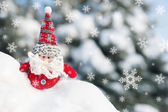 Santa toy in snowdrift with snowfall — Stock Photo