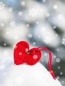 Rotes herz spielzeug in schneefälle auf tanne — Stockfoto