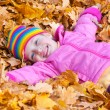 Girl lies on yellow leaves in autumn park — Stock Photo