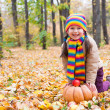Girl in autumn park with pumpkin and apples — Stockfoto