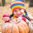 Girl in autumn park with pumpkin and apple — Stock Photo