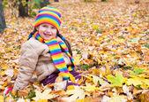 Kız sarı yapraklar sonbaharda parkta oturmak — Stok fotoğraf