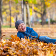 Boy lies on yellow leaves in autumn park — Stock Photo