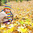 Girl sit on yellow leaves in autumn park — Stock Photo