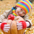 Girl in autumn park with pumpkin and apples — Stok fotoğraf