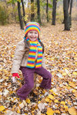 Girl sitting on stump in autumn park — Stock Photo