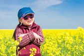 Girl in yellow field of rape — Stockfoto