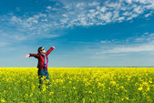 Woman in yellow field of rape — Foto Stock