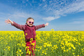 Girl in yellow field of rape — Foto Stock