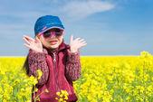 Girl in yellow field of rape — Stock Photo